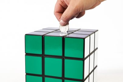 Uniquely Geek Rubrics Cube coin bank staged hand